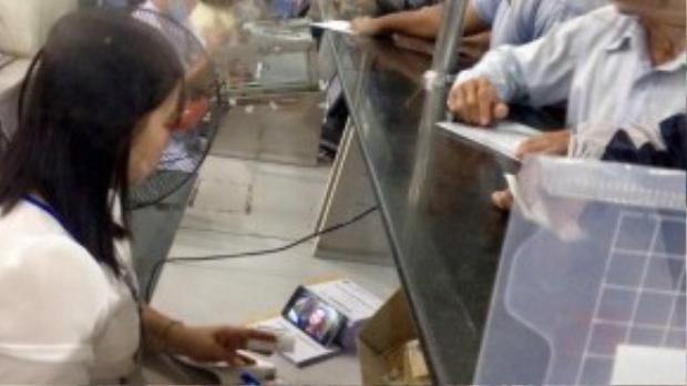 Nhân viên thu ngân chăm chú xem phim khi đang tiếp bệnh nhân (ảnh Facebook).