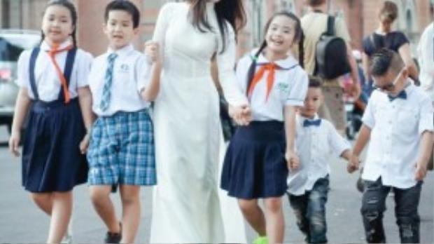 Hòa Minzy lựa chọn chiếc áo dài trắng duyên dáng bên cạnh các học trò. Trang phục của NTK Minh Châu đã giúp Hòa Minzy gây chú ý tại khu vực Nhà thờ Đức Bà.