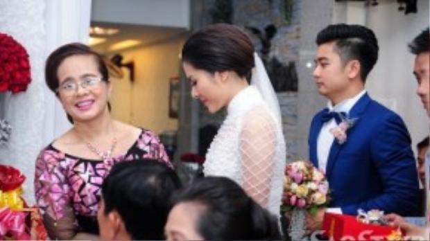 Vân Trang được mẹ đưa ra phòng khách để ra mắt hai họ. Cô diện áo dài trắng đính hạt pha lê trông rạng rỡ.