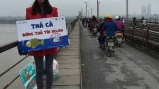 """SV Nguyễn Thị Hà Giang, năm thứ hai trường ĐH Lao động xã hội với tấm biển kêu gọi """"Thả cá đừng thả túi nilon"""" và chiếc túi to để thu gom túi nilon của người dân đi thả cá."""