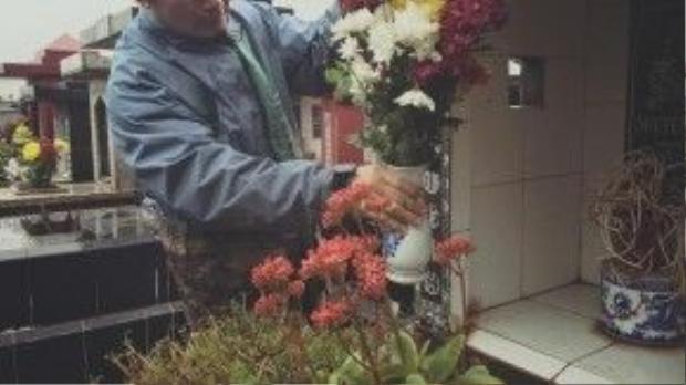 Bức ảnh đăng kèm dòng chia sẻ trên, ghi lại cảnh người đàn ông trung niên đang nức nở đặt bình hoa tươi lên mộ vợ mình.