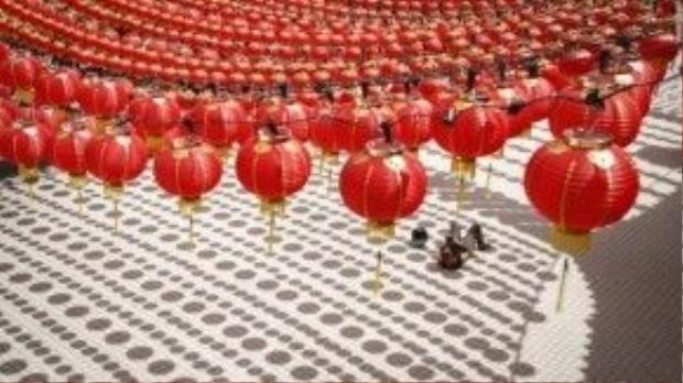 Một khách du lịch nằm hẳn xuống dưới đất để chụp giàn đèn lồng đỏ ở thủ đô Kuala Lumpur, Malaysia.