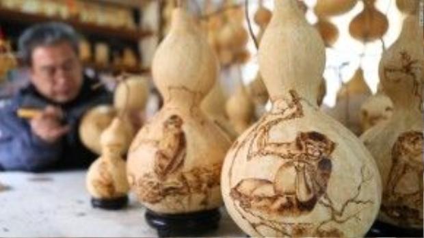 Một nghệ nhân đang vẽ hình các chú khỉ lên những quả hồ lô làm quà lưu niệm.
