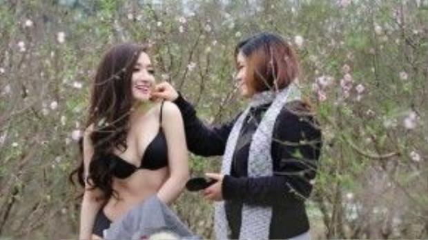 Cô gái trong hình mặc bộ bikini màu đen, có gương mặt ưa nhìn và thân hình cân đối, tươi cười tạo dáng giữa những cành đào.