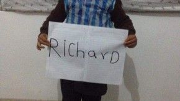 Cậu bé xinh xắn cầm tờ giấy có tên phóng viên nước ngoài.