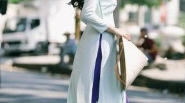 """Mái tóc dài được uốn lọn to bồng bềnh, xõa ngang bờ vai là phong cách thường thấy ở những quý cô thập niên 90. Trong shoot ảnh này, giọng ca """"Bỏ lại"""" trang điểm nhẹ nhàng để phù hợp với chiếc áo dài trắng nền nã, thanh lịch. Ảnh: Chanh Nguyễn."""