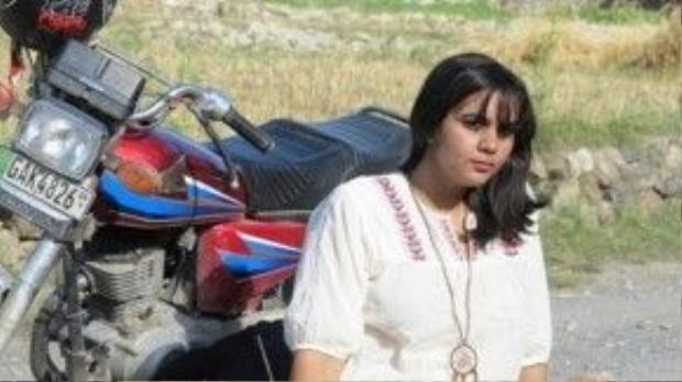 Cô gái trẻ và chiếc xe gắn máy của mình.