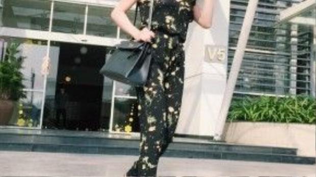 Nguyên cây jumpsuit gam màu đen tuyền điểm xuyết bằng những cánh hoa vàng trẻ trung, nữ tính , đôi gót hoa mũi nhọn cùng túi Hermes Kelly tạo cảm giác sang trọng và cuốn hút tuyệt đối choTrà Ngọc Hằng.