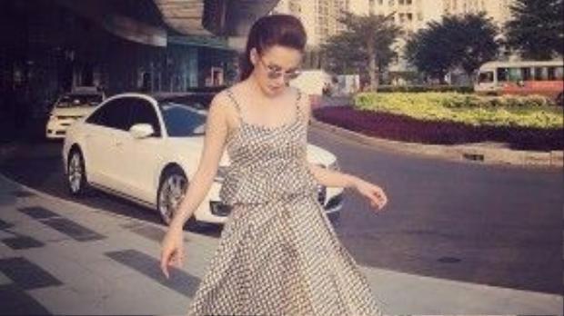 Chỉ cần một chiếc đầm họa tiết ô window mang hơi hướng cổ điển, Angela Phương Trinh đã ghi điểm tuyệt đối với phong cách đơn giản nhưng rất sang trọng. Để trông có vẻ điệu đà hơn một tí, cô nàng chọn phụ kiện kính mắt gương cùng tông với tổng thể trang phục.