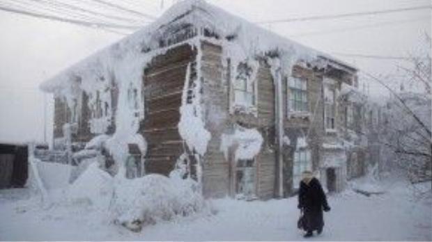 Người phụ nữ đi qua một ngôi nhà đông lạnh giữa làng.