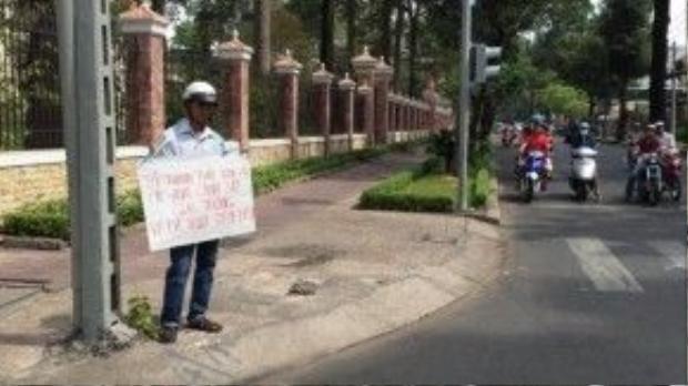 Anh Điền với tấm bảng xin lỗi cảnh sát giao thông trên đường Nguyễn Đình Chiểu, Q.3, TP HCM sáng 12/2.