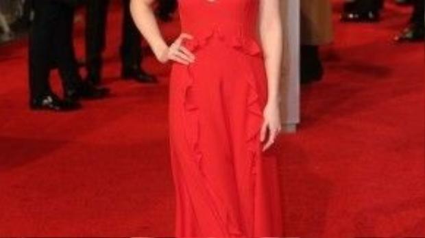 Tại sự kiện 2016 BAFTA, Dakota Johnson chọn chiếc váy của nhãn hàng Dior màu đỏ quyến rũ có tạo nhấn bèo chạy dọc thân váy.