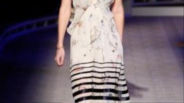 Gigi Hadid mở màn show diễn trong chiếc váy voan kẻ sọc, vừa nữ tính lại vừa cá tính.