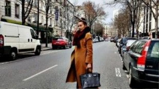 Thanh Hằng diện chiếc trench-coat màu camel - item cực hot hiện nay. Cô kết hợp cùng túi xách Hermes Birkin màu đen da togo và giày sneaker năng động.