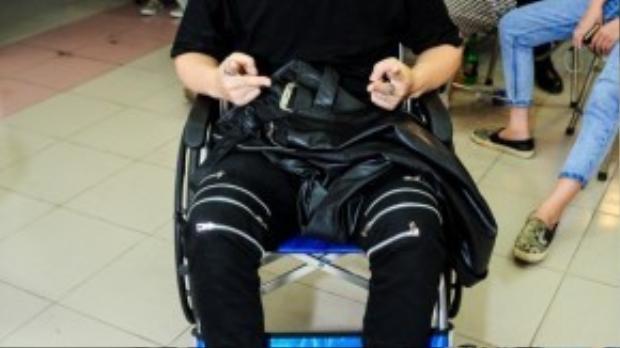 YanBi trong hậu trường ngồi trên xe lăn, anh bị chấn thương nặng ở chân trong quá trình chuẩn bị cho cuộc thi X-factornăm nay.