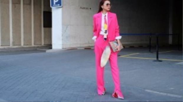Thanh Hằng nổi bần bật giữa đường phố Paris với mộ pant-suit màu hồng bắt mắt. Cô sử dụng clutch cầm tay và giày từ thương hiệu Gucci.