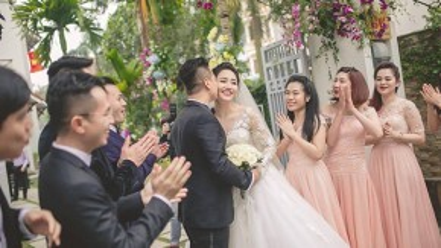 Trà My không giấu được niềm hạnh phúc khi được ông xã Lê Hoàn âu yếm hôn má.