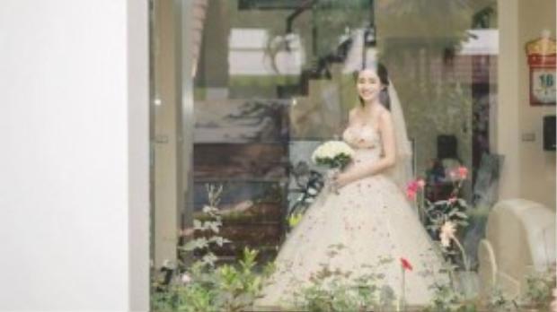 Chiếc váy cưới đơn giản màu kem với nhiều chi tiết hoa màu đỏ điểm xuyết phần thân áo