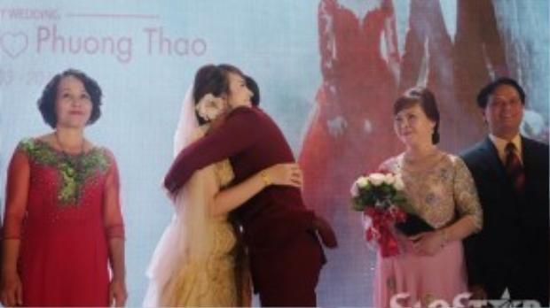 Khoảnh khắc hai vợ chồng hôn và ôm nhau hạnh phúc trong sự chứng kiến của gia đình hai bên, bạn bè đồng nghiệp.