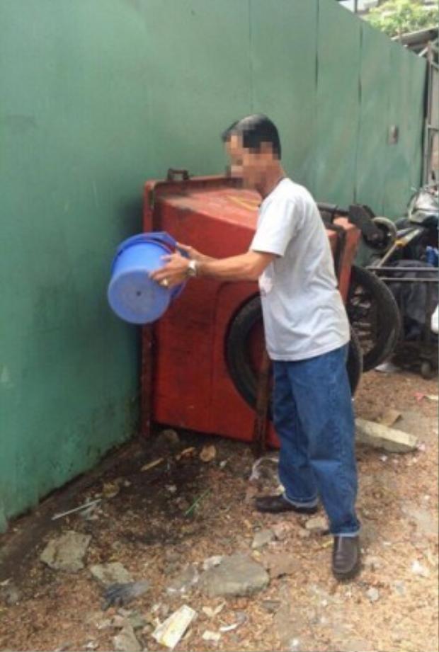 """Một người dân """"tè bậy"""" bị cơ quan chức năng yêu cầu đi lấy nước dội sạch khu vực."""