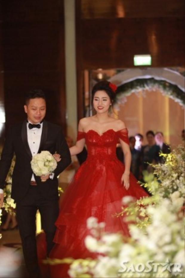 Trước phần thực hiện các nghi lễ trong tiệc cưới, Á hậu Hoàn vũ Việt Nam 2015 tranh thủ thay bộ trang phục màu đỏ bắt mắt, nổi bật.