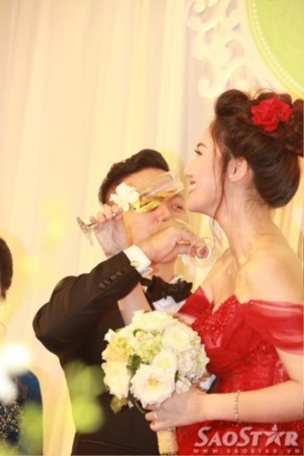 Cặp đôi vui vẻ tiến hành các nghi thức trong tiệc cưới trước sự chứng kiến của gia đình hai bên, báo giới và quan khách.
