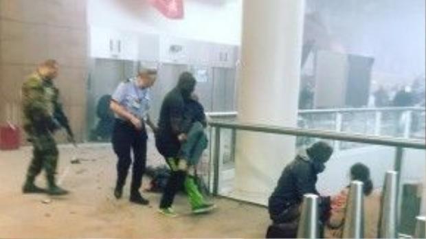 Alphonse (quần đen-xanh) hỗ trợ đưa các nạn nhân tới nơi an toàn trước khi cảnh sát và cứu hộ đến.
