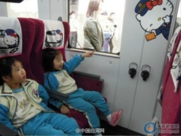 Các hành khách nhí thích thú ngắm nhìn những chiếc khăn tựa đầu có in hình mèo Kitty.