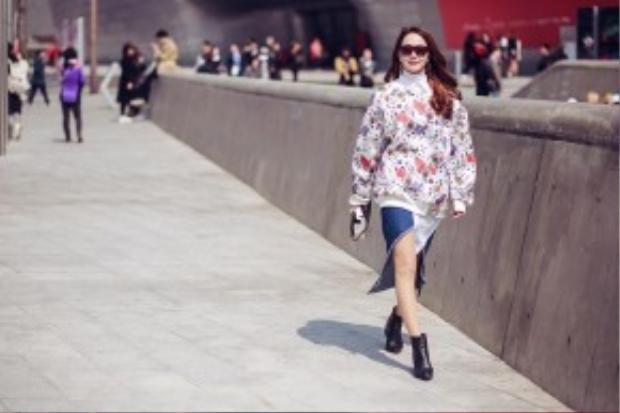 Minh Hằng khoe streetstyle cực chất trên đường phố Seoul. Cô nàng diện chân váy denim dáng mullet phối cùng sweater hoạ tiết.