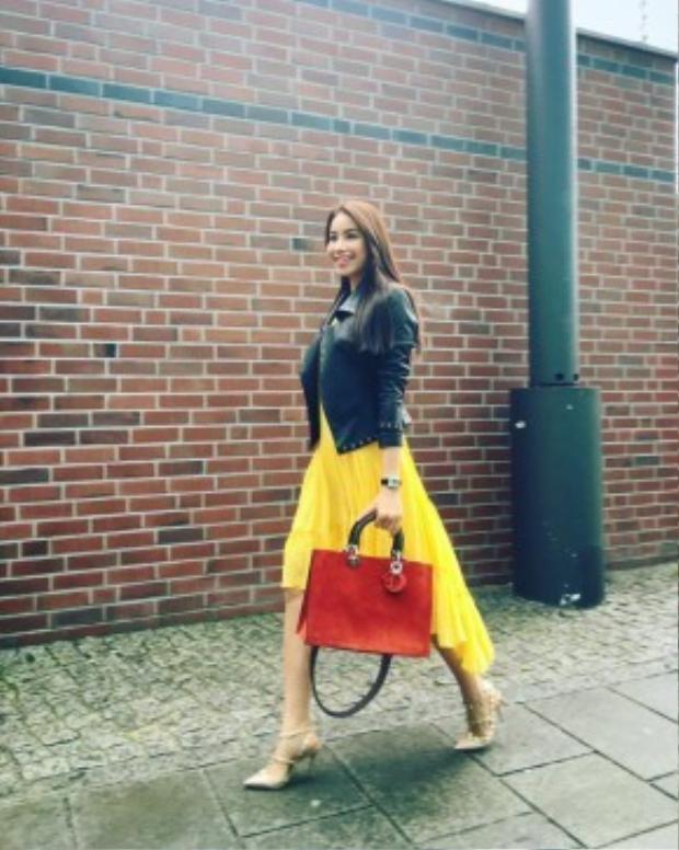 Vẫn là váy xếp ly nhưng Hoa hậu Phạm Hương lại chọn cách phối tương phản với túi Dior cùng jacket da.