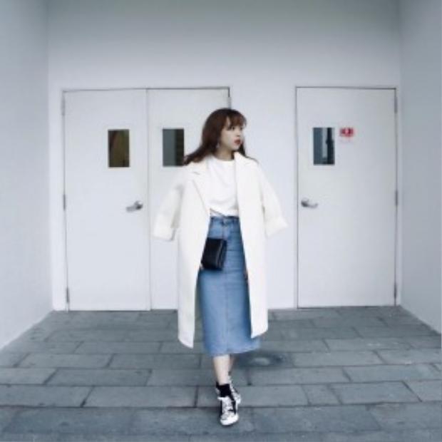 Cô bạn này lại vô cùng thanh lịch với set đồ gồm trench coat dáng dài phối cùng chân váy denim dáng bút chì cùng giày sneaker.