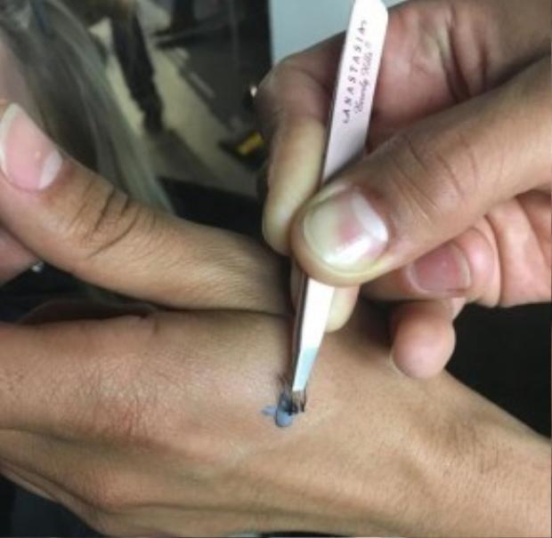 Chuyên gia trang điểm Vincent Oquendo chấm keo vào từng cụm mi giả…