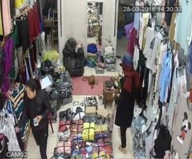 Người phụ nữ ăn mặc lịch sự, đội mũ bảo hiểm bước vào cửa hàng quần áo thời trang. (Ảnh cắt từ clip)