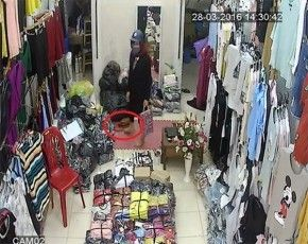 Người phụ nữ phát hiện ra chiếc túi dưới sàn và đá vào góc khuất, tránh sự chú ý của mọi người. (Ảnh cắt từ clip)