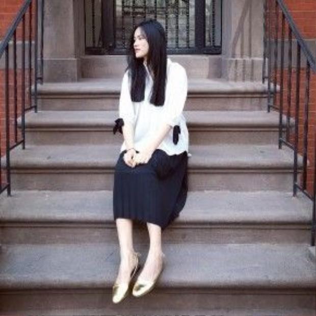 Chỉ với chiếc áo sơ mi trắng oversize cùng chân váy xếp ly đen, Tuyết Lan đã có ngay một bộ trang phục vừa thoải mái vừa ưa nhìn. Điểm nhấn của bộ trang phục là đôi giày bệt ánh kim cùng phần nơ đính ở tay áo.