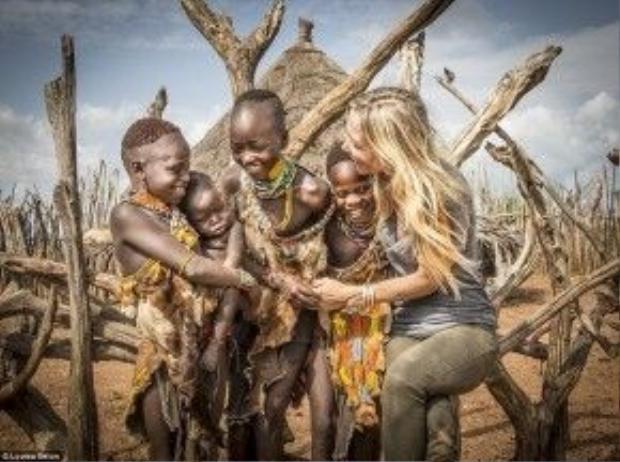 """Seton cho biết: """"Chụp trẻ em dễ nhất, vì chúng thích cười đùa với tôi. Chúng rất thích ngắm và chạm vào mái tóc màu vàng của tôi. Đứa bé này sợ màu da trắng của tôi và đã khóc thét khi được đưa cho tôi bế""""."""