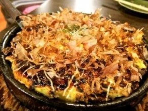Bánh xèo Nhật trông như một chiếc pizza với những nguyên liệu như: bột khoai nghiền, trứng, bạch tuộc xé, bắp cải xắt sợi, thịt heo…