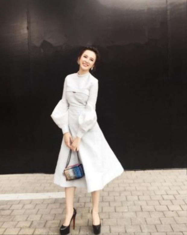 Angela Phương Trinh thanh lịch trong chiếc váy trắng dáng xoè cách điệu tay chuông. Cô nàng ngày càng trở nên kín đáo, thuỳ mị trong phong cách ăn mặc gần đây.