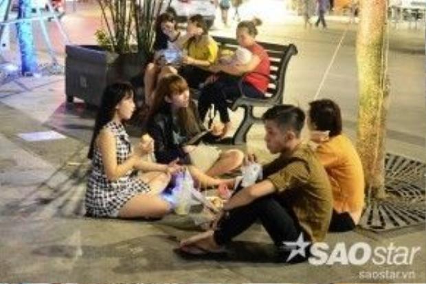 Nhóm 4 bạn trẻ bày đồ ăn, thức uống xuống mặt đường phố đi bộ rồi vui vẻ trò chuyện.