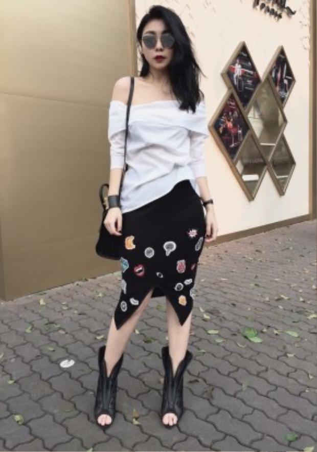 Fashionista Trang Trần với outfit cực chất mang hơi hướng goth pha chút punk lạnh lùng. Cô nàng kết hợp áo trễ vai cùng chân váy tulip đính nạm logo lạ mắt. Điểm nhấn là đôi bốt da nổi bật cùng phụ kiện kính mát Gentle Monster thời thượng, túi xách Saint Laurent 'Sac de jour', vòng tay Hermes.
