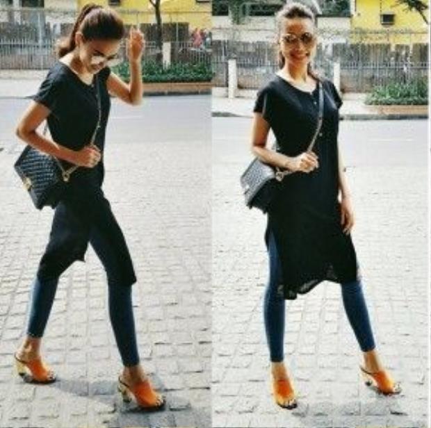 Thanh Hằng luôn khiến mọi người không thể rời mắt với mỗi lần xuất hiện dù là trên thảm đỏ hay ngoài đường phố. Siêu mẫu diện T-shirt dáng dài xẻ vạt kết hợp với quần skinny jean. Điểm nhấn của cả bộ trang phục là cặp kính mát tròng cam tiệp màu với đôi giày mules.