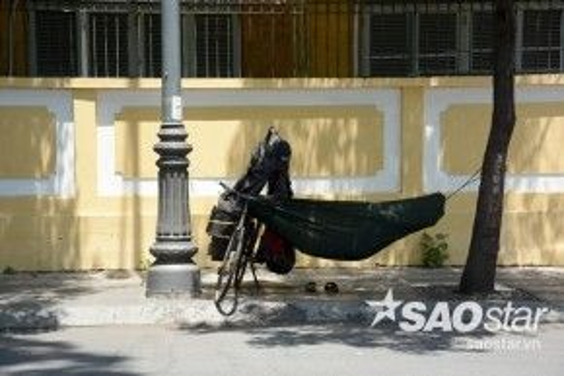 Một người vô gia cư mắc võng dưới bóng râm nghỉ trưa trên đường Võ Thị Sáu, quận 3.