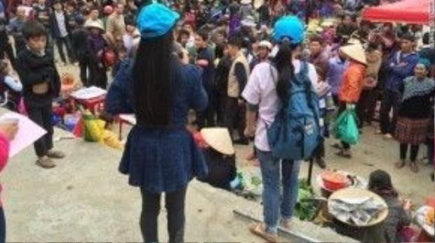Hai cô gái từng là nạn nhân của bọn buôn người tuyên truyền cho người dân trong chợ Bắc Hà. Ảnh: CNN