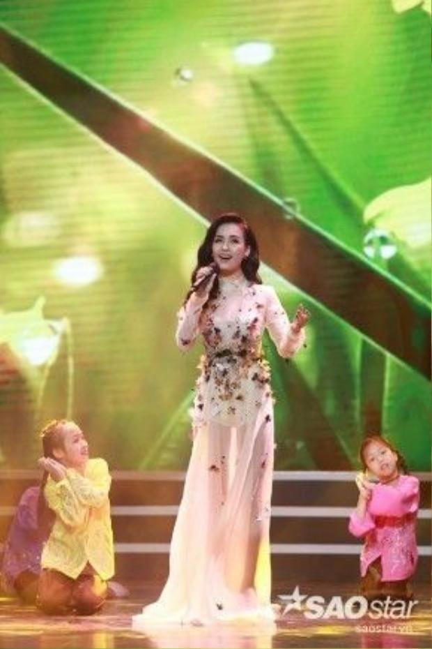 Ngay sau đó, cô thay một bộ đầm khác khi trình diễn ca khúc Tôi thấy hoa vàng trên cỏ xanhtrong chương trình.