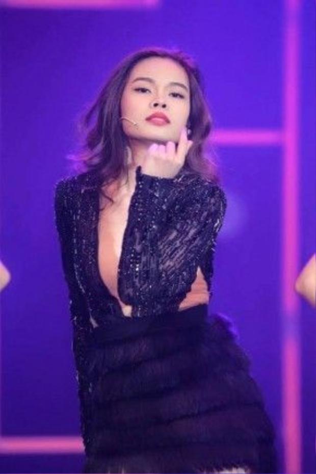 Thi thoảng cô ca sĩ sinh năm 1989 sẽ xuất hiện cá tính hơn một chút với jumpsuit đen được khoét sâu phần ngực và phần thân dưới làm từ lông vũ.