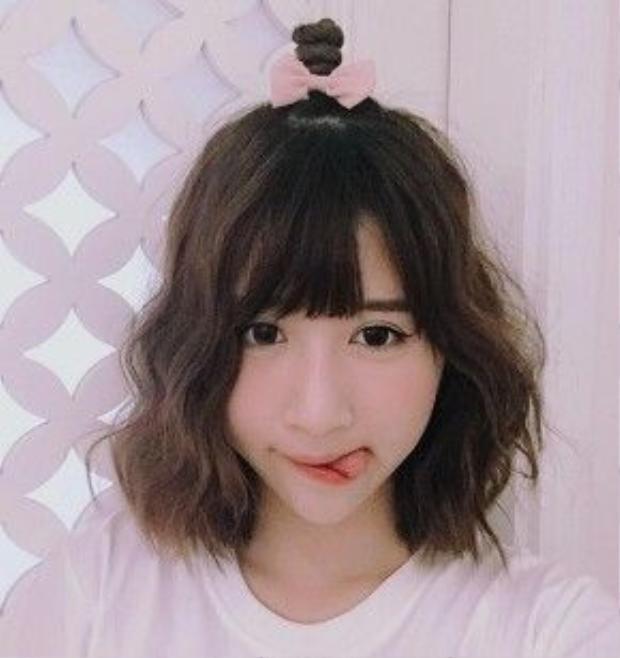 Nàng Quỳnh Anh Shyn chính là người đi đầu trào lưu tóc búi nửa đầu trong giới trẻ Việt. Với tóc bob mái thưa điệu đà, cô nàng phá cách khi lấy một phần tóc phía trên búi gọn lên trên đỉnh đầu, cố định bằng 1 chiếc chun buộc tóc dễ thương.