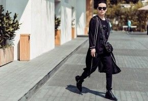Fashionisto Kelbin Lei trung thành với màu đen như mọi lần. Anh chàng này luôn tạo được sức hút cho người đối diện. Áo choàng cách điệu mặc bên ngoài chính là một sản phẩm do anh tự thiết kế.