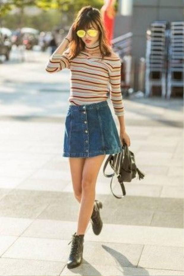 Người mẫu Cao Thiên Trang với chân váy jean đơn giản cùng áo sọc ngang trễ vai.