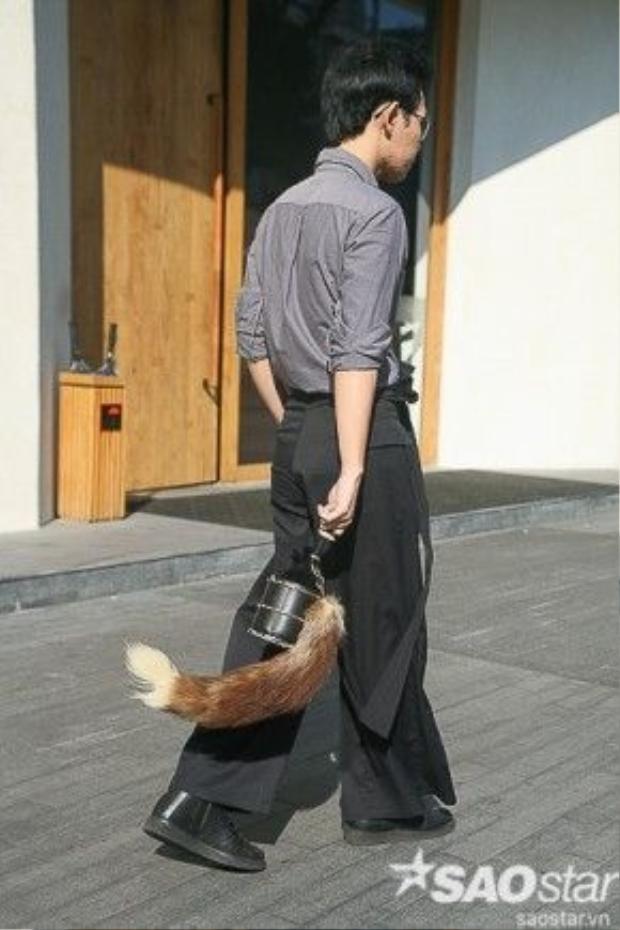 Túi xách là một trong những phụ kiện không thể thiếu để hoàn thiện set đồ. Anh chàng này điểm thêm cho chiếc túi xách mini dáng hộp của mình một chiếc đuôi chồn đẹp mắt.