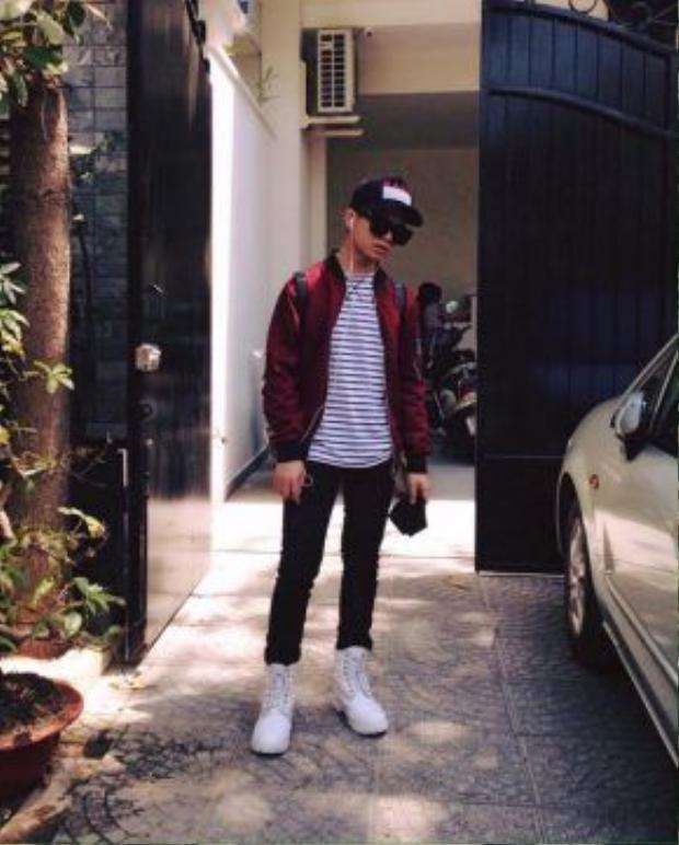 """Quang Anh chọn áo thun họa tiết kẻ ngang trắng đen mix với áo bomber đỏ mận và không quên mang theo chiếc mũ giúp """"phớt lờ"""" cả nắng hè lẫn mưa giông Sài Gòn những ngày thời tiết thất thường."""